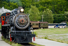 Train and Tour Buses. An old vintage steam train and tour buses in Skagway Alaska stock photo