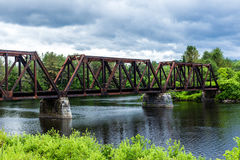 A train track crossing over a New Hampshire river on bright cloudy blue day.  royalty free stock image