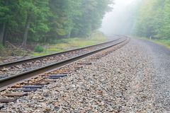 Train track into the fog. Train track at the Schunemunk mountain royalty free stock image