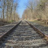 Train track with its rails rails, the sleepers and small stones, losing themselves on the horizon with a blurred background. Beautiful day in South Limburg in royalty free stock photography