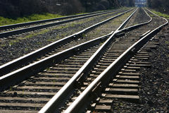 Train Track Junction. Two train tracks going off into the distance, one splits into a third track Royalty Free Stock Photography