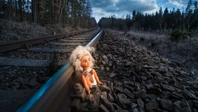 Train track with old doll lit by mystery light. Broken abandoned child toy at the rusty rail in dark forest. Idea of fate, apocalypse, sci-fi, war or abuse Stock Image