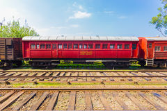 Train Track Passenger Carriage Sri Lanka Railway H. Side view of an old stationary red passenger carriage car sitting parked on train tracks, part of Sri Lanka Stock Image