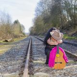 Train track with a woman with long black hair, black transparent dress, behind of a pink shawl, a brown hat and a guitar. On an autumn day with blurred royalty free stock photos