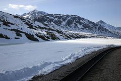 Train Tracks in Alaska. Train tracks through snow and sun in Alaska Stock Photos