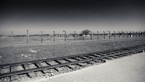 Train tracks and barbed wire fencing, Birkenau Concentration Camp, Poland Stock Photos