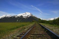 Train tracks in Chugach National Forest. Train tracks along Seward Highway, which follows Turnagain Arm in Chugach National Forest near Anchorage, Alaska stock photo