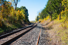 Train tracks curving left with telegraph poles on right Royalty Free Stock Images
