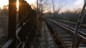 Train Tracks At Dusk. The train tracks on an old bridge. The sun falls to the bottom on a beautiful afternoon stock footage