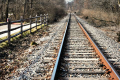 Train Tracks. And fence leading into the woods royalty free stock photo