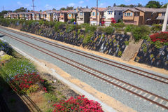 Train tracks with flowers and tract houses. Two rows of train tracks with flowers in the foreground and tract houses in the background Royalty Free Stock Photography