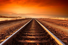 Train tracks goes to horizon in the majestic sunset. Royalty Free Stock Images