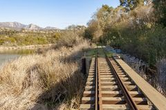 Train tracks with lake and trees royalty free stock photo
