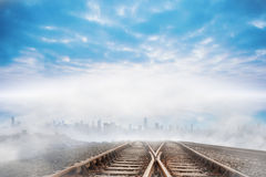Train tracks leading to city on the horizon Stock Image