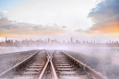 Train tracks leading to misty city Royalty Free Stock Images