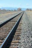 Train tracks leading to the mountain range Stock Photos