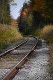 Train tracks leading into the wilderness of ADK. Quiet, peaceful image of train tracks that lead deep into Adirondack wilderness, fall colors on trees, copyspace Royalty Free Stock Photos