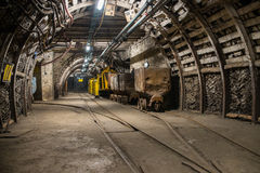 Train on tracks in mine. Fisheye view of coal cart located in corridor in modern coal mine, tracks and elements of internal infrastructure visible royalty free stock photos
