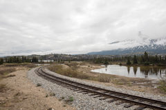 Train tracks in the mountains. Train tracks winding through barren landscape, with reflecting pond and snow-capped mountains in the background Stock Images