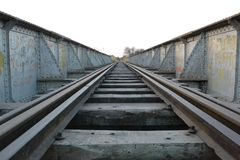 train tracks moving away towards the metallic colored horizon and over worn woods Royalty Free Stock Image