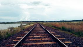 Train tracks near a river and near a field. A cloudy sky illuminates some beautiful roads that indicate the end of a long road. On the right a large mass of royalty free stock photography