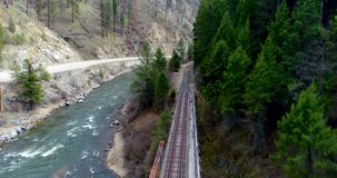 Train tracks with no trust-passing sign goes over a river. Rood railroad trestle leads over a wild Idaho river into a forest stock footage
