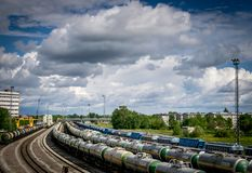 Aerial view of train tracks and wagons with big fluffy white clouds. royalty free stock images