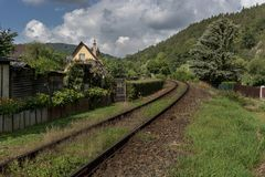 Train tracks overgrown with grass running past the house. Of the Sazava River valley royalty free stock photography