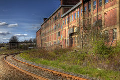 Train Tracks Pass Building. Train tracks pass an old brick building Royalty Free Stock Photos