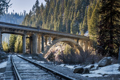 Train Tracks pass under a mountain bridge Royalty Free Stock Images