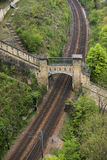 Train tracks passing under old ruins royalty free stock image