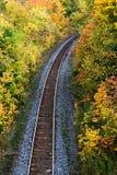 Train tracks run through autumn. Railway tracks and color on trees in fall Stock Photos