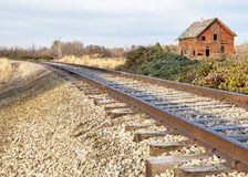 Train tracks run through the country near a house royalty free stock photography