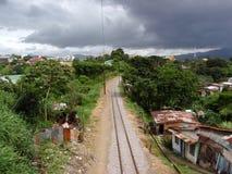 Train tracks run into the distance though neighborhood. SAN JOSE, COSTA RICA - JULY 13: Train tracks run into the distance though neighborhood on a cloudy day Stock Image