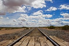 Train Tracks to Horizon with Fluffy Clouds Royalty Free Stock Photos