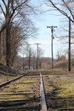 Train tracks to nowhere in fall. Old, unused train tracks with bare fall trees Royalty Free Stock Photos