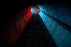 Train Tracks And Tunnel Split Choices. A brick underground train tunnel  that splits into two directions in the distance each distinctly coloured blue and red Royalty Free Stock Image