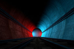 Train Tracks And Tunnel Split Choices. A brick underground train tunnel  that splits into two directions in the distance each distinctly coloured blue and red Royalty Free Stock Photography