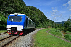 Train transportation service in rural tropical areas with river next to the rail track Royalty Free Stock Image
