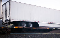 Train transporting semi trailer by railroad on open platform Stock Photos