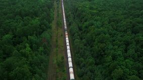 The train transports tanks of crude oil among virgin ecological green forests. Aerial view.