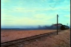 Train traveling down railroad track stock footage