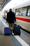 Train traveller. Senior traveller carrying 2 luggages in a hurry to board a waiting high-speed train Royalty Free Stock Image