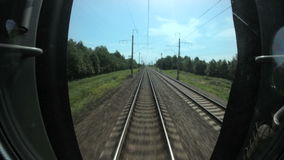 Train travels along rails between trees, railway communications stock video