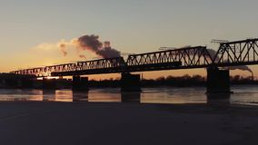 Train travels on bridge. Train travels over the bridge against the sky, sun and river. Novosibirsk, Russia. Full HD Resolution 1920×1080 Video Frame Rate 29 stock video