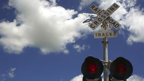 A train trips the signal while switching cars in a Texas town. Lights flash fast at a railroad crossing as clouds roll by stock footage