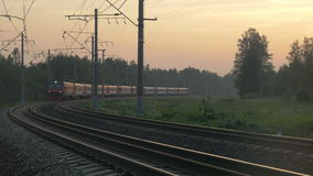 Train turning and passing by outside the town. Evening passenger train going across the countryside. Close view of carriages and wheels as it passing by stock video