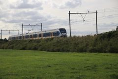 Train type SLT light rail of the NS running at the railroad track in Nieuwerkerk aan den IJssel in the Netherlands.  royalty free stock photo