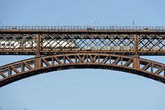 Train under cars on iron bridge over Adda river at Paderno, Italy Royalty Free Stock Images