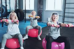 Joyful retired ladies lifting dumbbells at gym. Train with us. Selective focus on two sporty senior women sitting on fitness balls and working with dumbbells Stock Photos